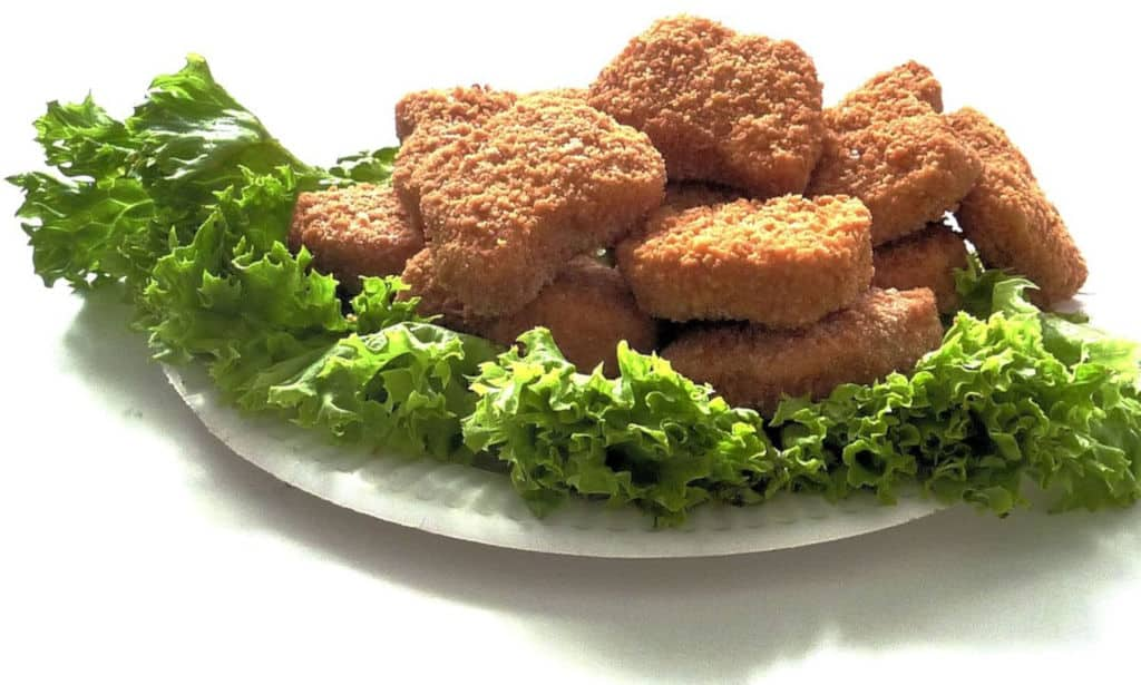 air fried chicken nuggets on a plate with salad dressing