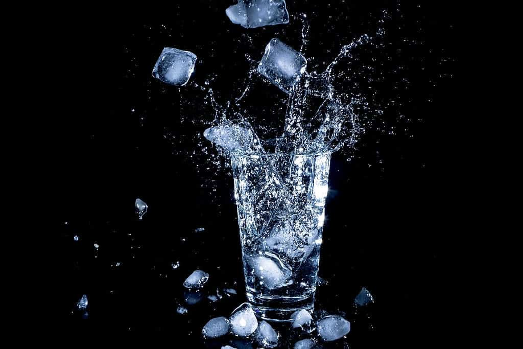 dropping ice cubes in a glass of water
