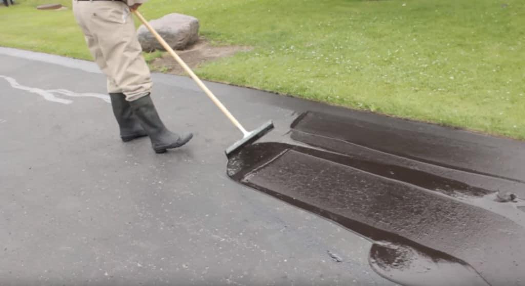 a man Sealing asphalt driveway