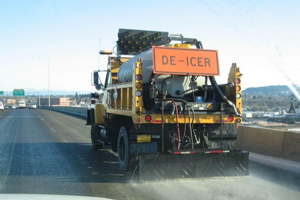deicer on the road spraying liquid ice melt