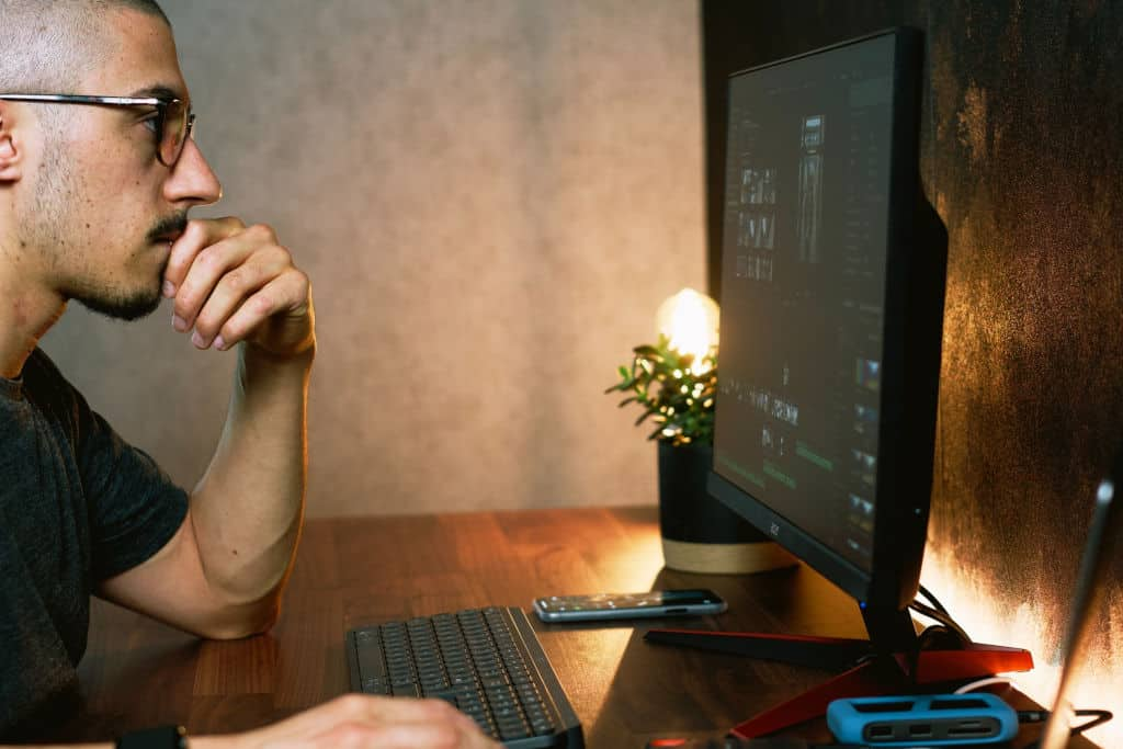 guy wearing glasses in front of computer